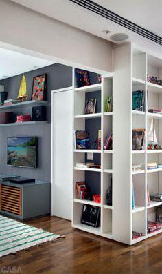 Boa ideia para reforçar a integração do estar com o escritório e amenizar a viga do teto: a estante faz um L. A porta ao lado do móvel leva ao quarto do casal. Um tom de grafite (pintura gofrato) unifica a marcenaria da TV. Na prateleira do alto, pôster do LZ Studio.