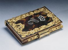 Queen Charlotte's Notebook. ca, 1765. Tortoiseshell and gold notebook case and pencil, applied with pierced floral scroll border, crown and C monogram set with brilliants at centre; spine in rose and yellow gold with bright cut panels imitating book spine. Gold clasp securing pierced pencil.