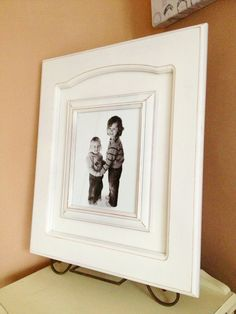 Beautifully simple rustic picture frame. Repurposed cupboard door. Hardware removed. Sand. Paint. Glue cheap wooden frame. Flat enamel white spray paint with light distressing.