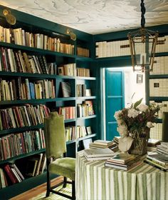 Designer Colette van den Thillart uses this room for her home office.    A blue lacquered wall and ceiling fresco are just two of the rich details that gives this room personality. The striped tablecloth and green velvet chair adds contrast. Gold shell-shaped lights shine on book spines for easy searching.