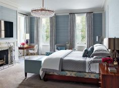 Traditional Bedroom by Steven Gambrel in New York, NY / Designed by S. R. Gambrel and crafted by Dune, the mahogany bed is upholstered in an Old World Weavers fabric and dressed with custom-made bedding by E. Braun & Co.; the curtains are of a de Le Cuona fabric, and a Samsung television is over the fireplace.      Designer: Steven Gambrel     Photographer: Eric Piansecki     Article: Forward Shift, February 2015     Location: New York, NY