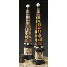 A pair of Italian Baroque style Pietra Dure obelisks, 19th century - the obelisks in geometrical shaped pietra dura inlaid with onyx, Siena and red marbles on slate, mounted with a circular finial raised on ball feet above a molded pedestal above a spreading base. - Dim. height 33 1/2 in.; width 5 1/2 in.; depth 5 1/2 in. (85 cm; 14 cm; 14 cm)