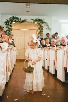 love the ribbon on the pews...which is actually chair ties, love the greenery over the door and the barefeet, heirloom dress