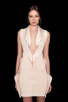 Structured symmetry minimal dress with gently rippled sculpted edges.