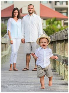 toddler boy in hat smiling with parents looking on in background during their beach family photoshoot. Family photography. beach photography.