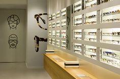 Interesante expositor gafas, buena iluminación y combina blanco con madera