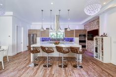 Give your kitchen a funky feel with retro leather bar stools and a pair of fun light fixtures.