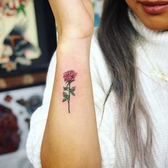 Red rose tattoo on the right forearm.