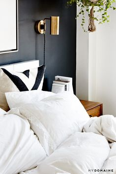 Black wall, Gold sconces, White bedding, Mid century bedside tables