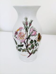 """Portmeirion  Botanic Garden Vase 8""""  WIth flowers from your garden, or just as it is, this lovely vase with a botanical print designed by Susan Williams-Elllis will add a cheery touch to your home. Portmeirion ware, with its charming botanical designs, sets the tone for a beautiful tablescape. The design appears on both sides and is of the Rosa Canina, or Dog Rose.  8"""" high, it features the 1972 marking and is in perfect condition. Bring your garden indoors and enjoy it daily with…"""
