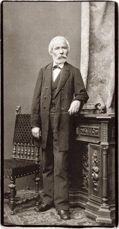 """Arany János utolsó fényképezkedése alkalmával, halála előtt két évvel készült ez a felvétel Ellinger Ede műtermében, több hasonló beállítással együtt. Közülük a legismertebb a """"botos és kalapos"""" portré, melyen az író szintén könyvekre támaszkodva áll, de kezében botot és kalapot tart. Erről írt Kosztolányi Dezső 1917-ben: """"Itt egy megható alakot bámulok, melyet alig-alig ismernek. A beesett, csontos arcot rövidre nyírt ősz szakáll keretezi, a hosszú haj csapzottan simul előre, a halántékra… Language And Literature, Heart Of Europe, Writers And Poets, Celebrity Gallery, Budapest, Old Photos, Famous People, Museum, Author"""