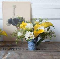 bright yellow mini calla lilies, white freesia and seeded eucalyptus.  My personal opinion ... this combination deserves a better vase :)