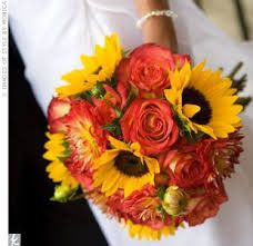 Round style bouquet with sunflower, roses and chrysanthemums(?).  This is lovely but might be a bit big. Is one of the sunflower bouquets I've seen that still looks 'classy' and not too 'quirky'.  Thinks its the balance of the roses that helps this.