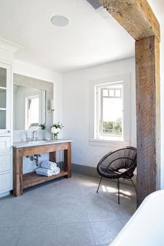 A wood beamed doorway opens to a rustic cottage bathroom filled with a reclaimed wood washstand topped with concrete under an inset mirror alongside a gray diamond pattern floor.