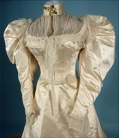 1894 Wedding Gown worn by Ester Maria Lewis Chapin (1871-1959), the great-great granddaughter of George Washington's sister, Elizabeth Washington Lewis (1722-1797).  Ester's father, Col. Edward Parke Custis Lewis (1837-1892) was the American Minister to Portugal under President Grover Cleveland from 1885-1889.  The gown is a beautiful ivory silk satin.  Boned high-neck bodice with huge gigot sleeves, front chiffon inset at yoke, waist, and cuffs.