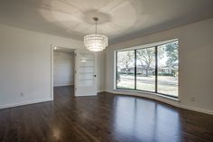 open floor plan living and dining rooms with modern finishes, bay window