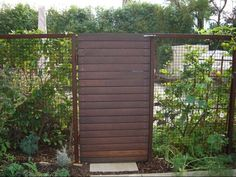 modern fencing | clean look with a gate of horizontal boards framed by a hogwire fence ...