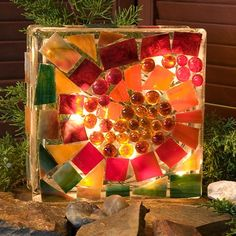 Using a simple glass block and a few glass mosaic pieces you can quickly put together a series of garden lamps for the warmer weather