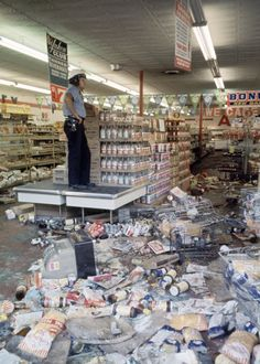 Detroit police officer standing guard over a grocery store, which was looted and damaged during the riot. 1967