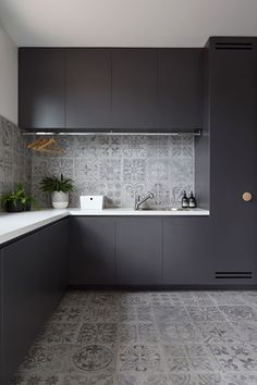 In this modern laundry room, matte black cabinets provide a strong contrast to the light grey tiles and the white countertops. A drying bar has been i… – Laundry Room Kitchen Design Small, Kitchen Design, Black Cabinets, Kitchen Room Design, Kitchen Remodel Layout, Modern Laundry Rooms, White Kitchen Backsplash, Kitchen Remodel Cost, Kitchen Furniture Design