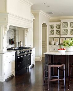 White kitchen with dark wood floors.  Like the detail on the upper cabinets.