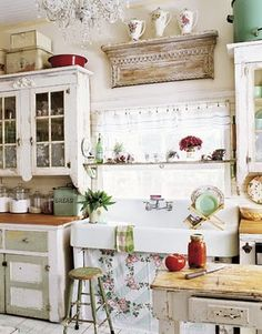 Love this shabby chic white kitchen! Distressed white cabinets, combined with a farmhouse sink and skirted is stunning.
