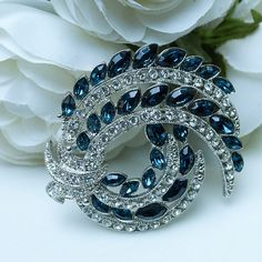 Beautiful swirl feather design of faceted sapphire rhinestone marquis and pave clear crystals. Vintage reproduction from the 70's.