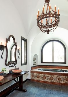 Spanish-style master bath with tiles built-in bathtub and gothic-style chandelier.