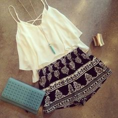 This here is a; White flowy crop-top with shorts that have certain patterns on it. Along with a long necklace with a straight blue pendant. Also with a gold sphere metal bracelet.