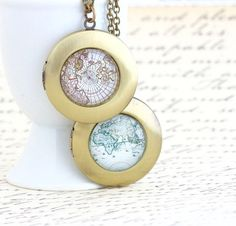 This unique, round brass map locket necklace boasts a vintage map print below a glass dome. The locket opens so that you can insert a photo inside, preserving those travel memories close to your heart