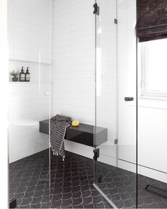 Contemporary black and white shower boasted black fan shaped floor tiles and white stacked wall tiles with a glossy floating shower bench. White Tile Shower, Shower Floor Tile, Black Shower, Shower Niche, Shower Seat, Black White Bathrooms, Shower Surround, Modern Shower, Bathroom Interior Design