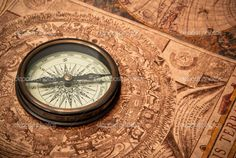 Antique Compasses Vintage   Antique compass lying on old style map. Sepia toned.