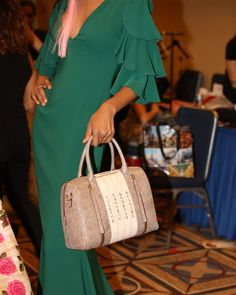 A model is holding a Bellorita brown hand tooled and hand painted calligraphy leather satchel bag.