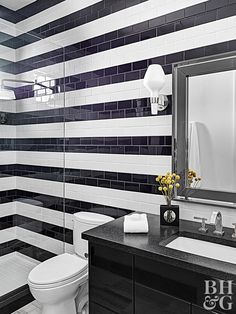 A glass shower wall is a great way to make a small bathroom feel large. This bathroom takes it a step further by continuing a black and white striped tile pattern from the walls into the shower. This technique eliminates the shower/bathroom barrier to make it feel like one big space.