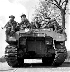 Personnel of the Royal Hamilton Light Infantry aboard 'Sherman' tank of 'B' Squadron, Fort Garry Horse, advancing to Groningen, Netherlands, 13 April 1945.