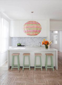 KITCHEN DESIGN IDEA: Marble splashbacks. Marble tiles in a fish-scale pattern combined with a statement light and pastel stools lend a playful nature in this kitchen by Sydney-based interior designer Stacey Kouros.