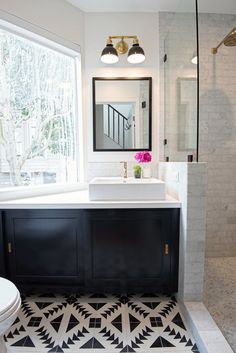 San Francisco Interior Design company Regan Baker Design -  Nopa Classic Casual Bathroom, Midcentury Modern, Black and White Cement Tile Shop Floor Tile, Marble Subway Tile, Brushed Brass Bathroom Fixtures, Dark Vanity Sliding Doors, Vanity Sconce