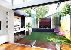 Small backyard connected with the interior using glass doors