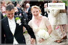 Laughing bride and groom walking through confetti shower at Downton on the Rock Church in Shropshire