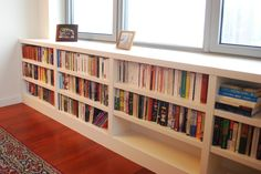 long low book shelves under window with clean top surface