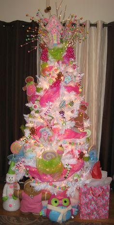 """2011 """"Candyland"""" inspired Christmas tree with a gingerbread family and house, candy canes, and other sweet treats!"""