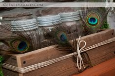 Wedding decor provided by Dressing Room No. 5.  Simple barnboard planter with antique mason jars and peacock feathers.