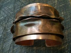 """A double copper cuff with leather under """"torn"""" top level."""