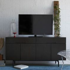 """60""""w x 17""""d x 30""""h.  we $900 Solid and engineered wood frame with Chocolate-stained veneer. Metal legs with brushed-Graphite finish."""