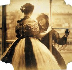 Two young women, one in a crinoline wedding dress and the other looking at her longingly through a window, photographed by pioneering Victorian photographer, Lady Clementina Hawarden.