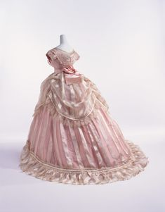 1866, France - Evening dress - Bodice of sheer ivory striped silk with pink silk taffeta; triple-layered skirt (sheer ivory striped silk skirt and overskirt, and pink silk taffeta underskirt); worn over large crinoline
