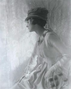 A contender for first fashion photographer was probably Baron Adolphe de Meyer who was hired by Conde Nast in 1913 to take experimental pictures for Vogue. His main characteristic was a wonderful use of backlighting and the soft-focus lens. Early fashion pictures were essentially society photographs of aristocrats, actresses and society models wearing their own clothes. The overall key of this photograph is a light grey, the only dark areas being around the sitters face, arms and lap