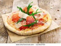Freshly prepared delicious pizza on oven paper with a golden base topped with tasty ham , cheeses, tomato and fresh green herbs - stock photo
