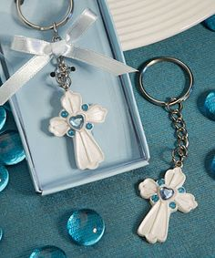 """Share the joy you're feeling on your new son's special day with these classic cross design spiritual occasion favors. Your family and friends will surely appreciate this useful and thoughtful keepsake. Each keychain favor measures 3.75"""" x 1"""" and has a detailed white poly resin cross charm with a central heart-shaped blue rhinestone bordered with round blue rhinestones, connected to a sturdy silver metal chain and ring. Perfect for baptism or first communion or any religious themed event…"""