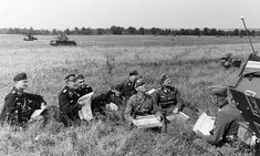 France, 1940: Erwin Rommel and his tank officers study the maps as Lutfwaffe flights interrupt the conference and all take a look at the sky. Rommel was always up front, racing up and down the line in his command car.